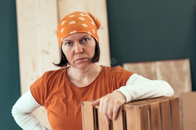 Het trotse vrouwelijke timmerman stellen met gebeëindigd houten krat stock foto