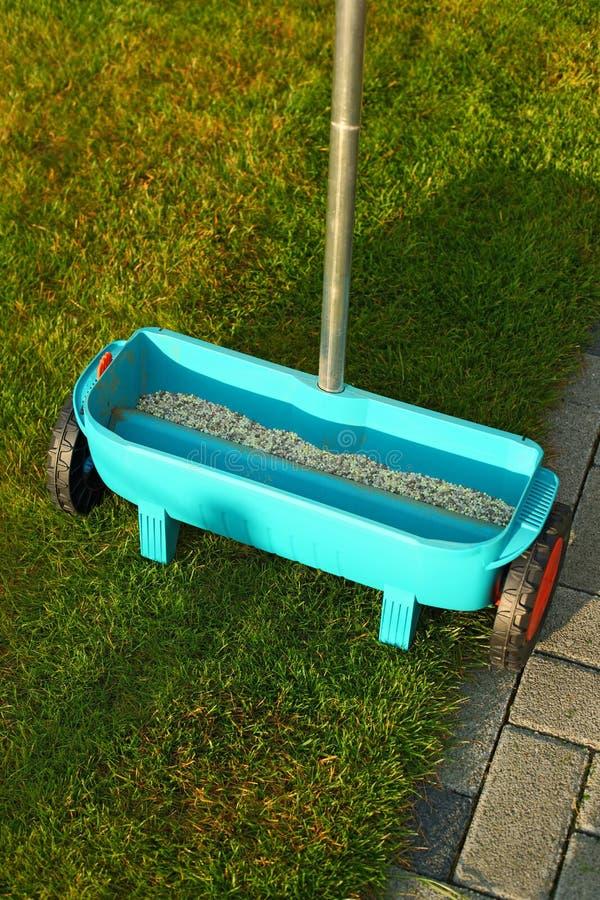 Het tuinieren - het bevruchten gazon stock afbeeldingen
