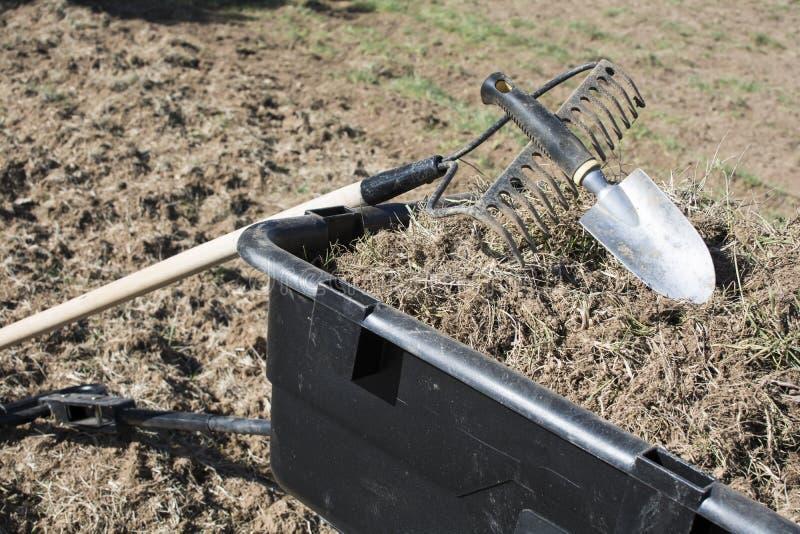 Het tuinieren hulpmiddelen op stapel van vuil en grassen royalty-vrije stock afbeeldingen