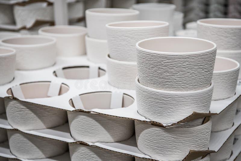 Het tuinieren, verkoop en consumentismeconcept - bloei potten op planken bij tuinwinkel royalty-vrije stock afbeelding