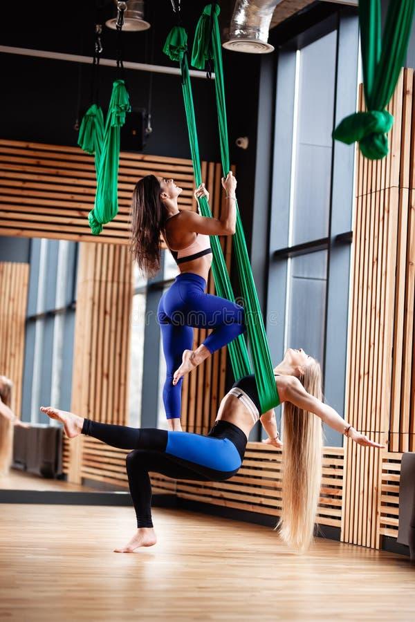 Het twee doen het jonge atletische meisjesbrunette en blonde geschiktheid op de groene luchtzijde in de moderne gymnastiek royalty-vrije stock afbeelding
