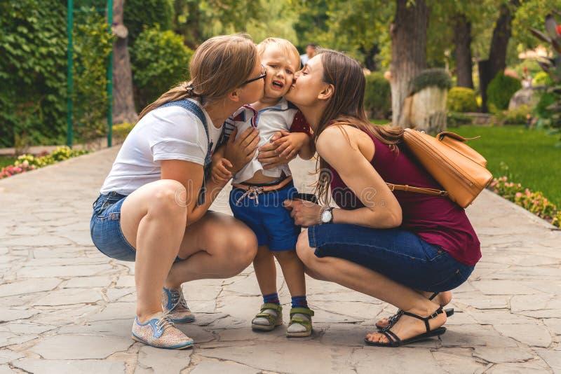 Het twee meisjesmamma kust hun wispelturig klein jongenskind in het park Niet een traditionele familie stock afbeelding