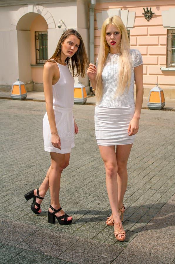 Het het twee vriendenblonde en brunette in wit kleden het stellen op de straat van de oude stad stock foto's