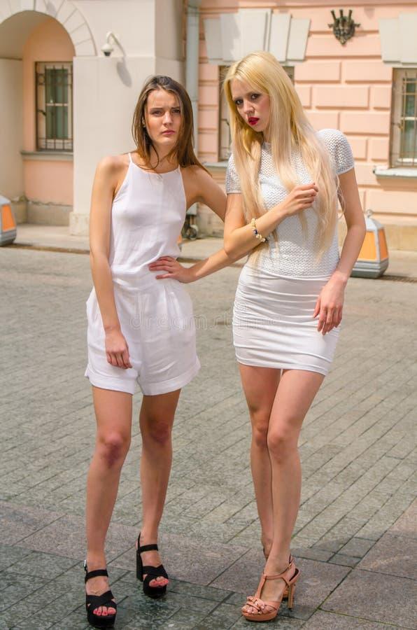 Het het twee vriendenblonde en brunette in wit kleden het stellen op de straat van de oude stad stock foto