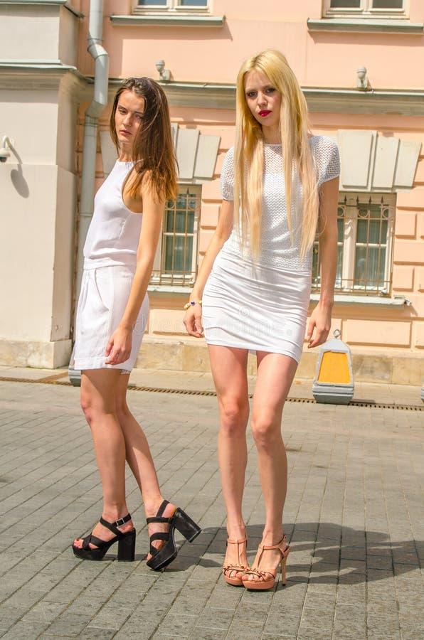 Het het twee vriendenblonde en brunette in wit kleden het stellen op de straat van de oude stad royalty-vrije stock foto