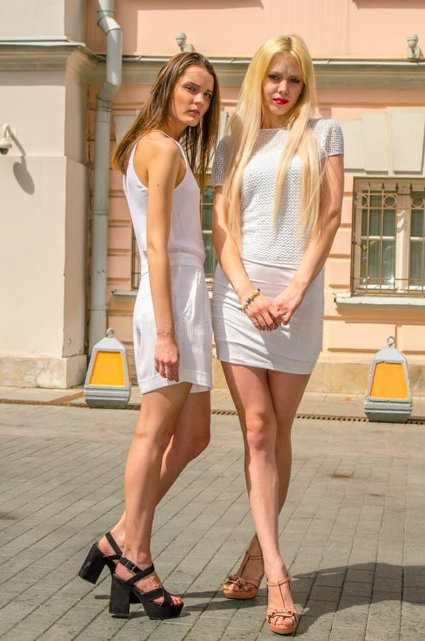 Het het twee vriendenblonde en brunette in wit kleden het stellen op de straat van de oude stad royalty-vrije stock afbeeldingen