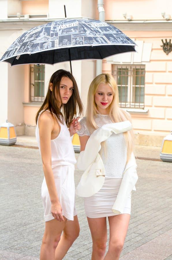 Het het twee vriendenblonde en brunette in wit kleden het verbergen van het weer onder een grote paraplu in de stegen van de oude royalty-vrije stock afbeeldingen