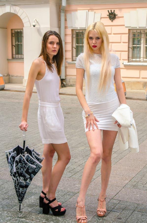 Het het twee vriendenblonde en brunette in wit kleden het verbergen van het weer onder een grote paraplu in de stegen van de oude royalty-vrije stock foto's