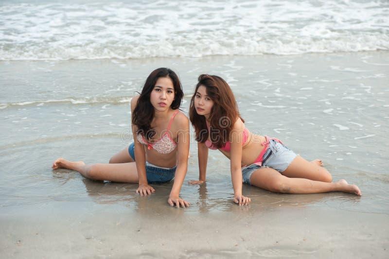 Het tweeling vrij Thaise vrouw stellen op het strand. stock foto's