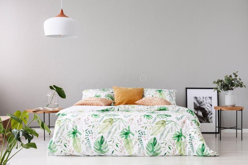 Het tweepersoonsbed met bloemendekbed en perzik kleurde hoofdkussen tussen twee houten nightstands met bloemen in vazen op het stock afbeeldingen