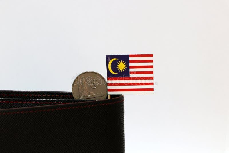Het twintig centenmuntstuk van Maleisië en de minivlag van Maleisië plakken op de zwarte portefeuille met witte achtergrond stock afbeeldingen