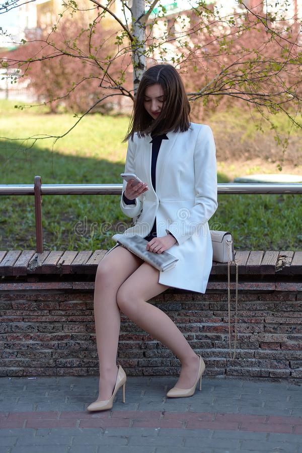 Het typen door mobiel Overseinen door mobiel Het donkere Haired Model van de Lingerie Modern stedelijk vrouwenportret royalty-vrije stock fotografie