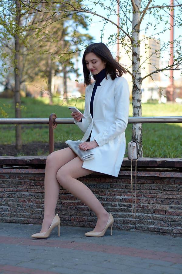 Het typen door mobiel Overseinen door mobiel Het donkere Haired Model van de Lingerie Modern stedelijk vrouwenportret stock afbeelding