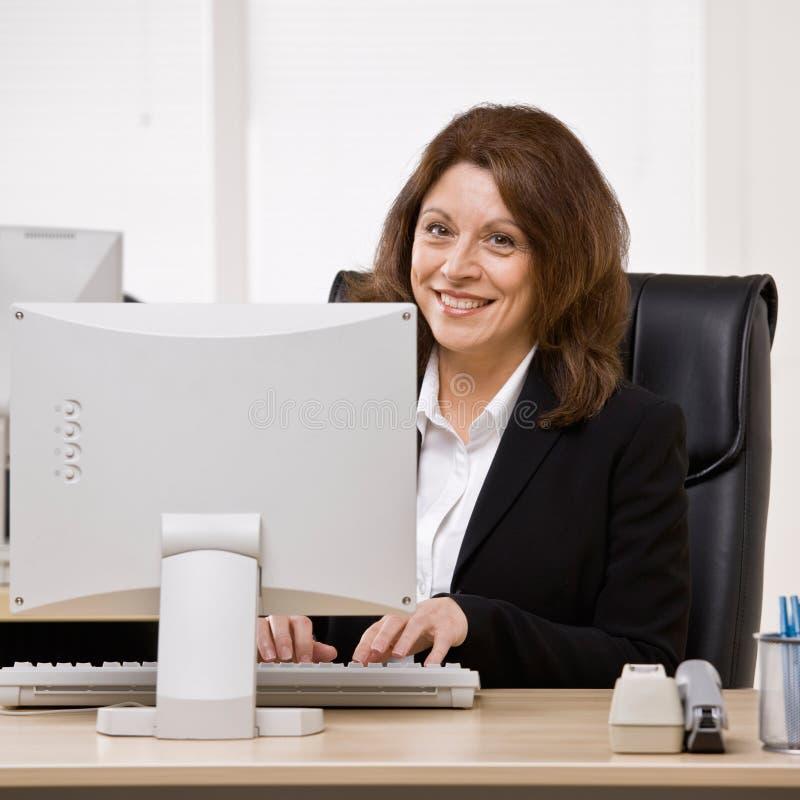 Het typen van de onderneemster op computer bij bureau stock foto