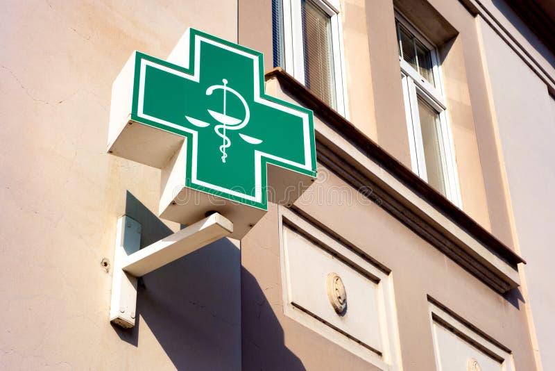 Het typische groene teken voor apotheken en healtcare verwante winkels stock afbeelding