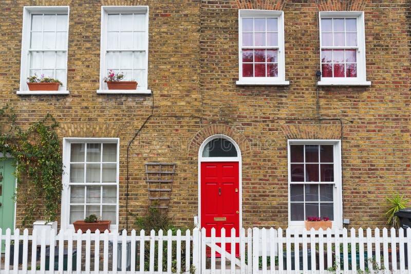 Het typische huis van Londen met bakstenen muur, rode deur en witte omheining stock afbeelding