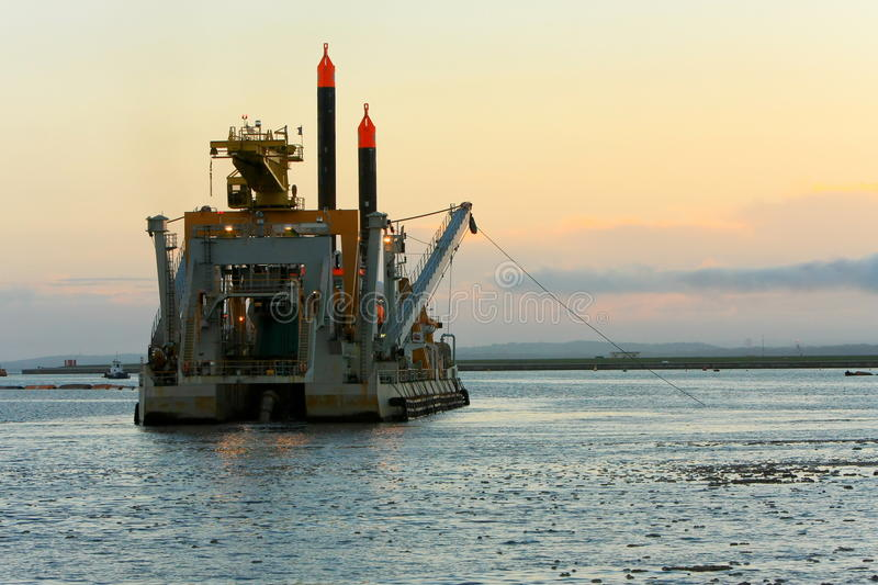 Het uitbaggeren van schip dat bij zonsondergang werkt. royalty-vrije stock fotografie