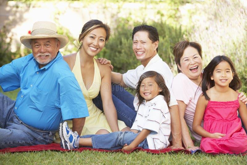 Het uitgebreide Ontspannen van de Groep van de Familie in Tuin stock afbeeldingen