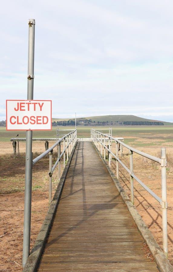 Het uitgedroogde meerbed met Pier sloot teken stock foto's
