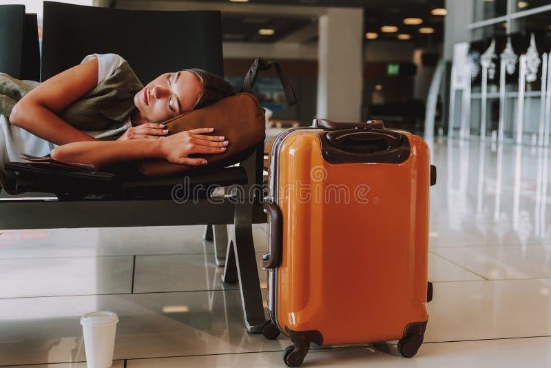 Het uitgeputte jonge meisje slaapt bij luchthaven stock foto