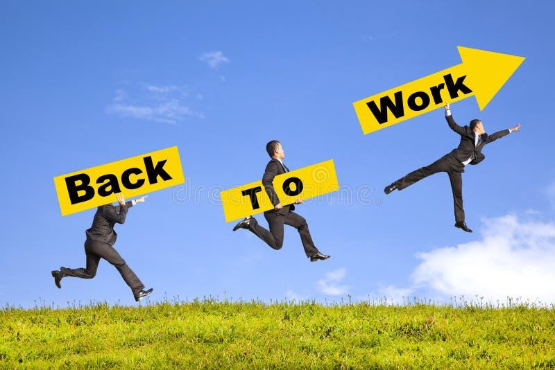 Het uithangbord van de zakenmanholding toont terug naar het werk stock foto