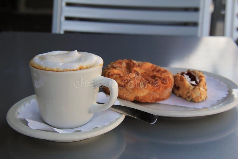 Het uitnodigen beeld van buitensporige gebakjes en het stomen latte royalty-vrije stock foto