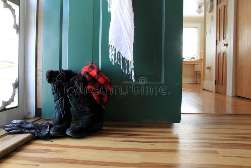 Het uitnodigen scène met de laarzen van de dameswinter, handschoenensjaal, en hoed dichtbij open deur van huis royalty-vrije stock foto's