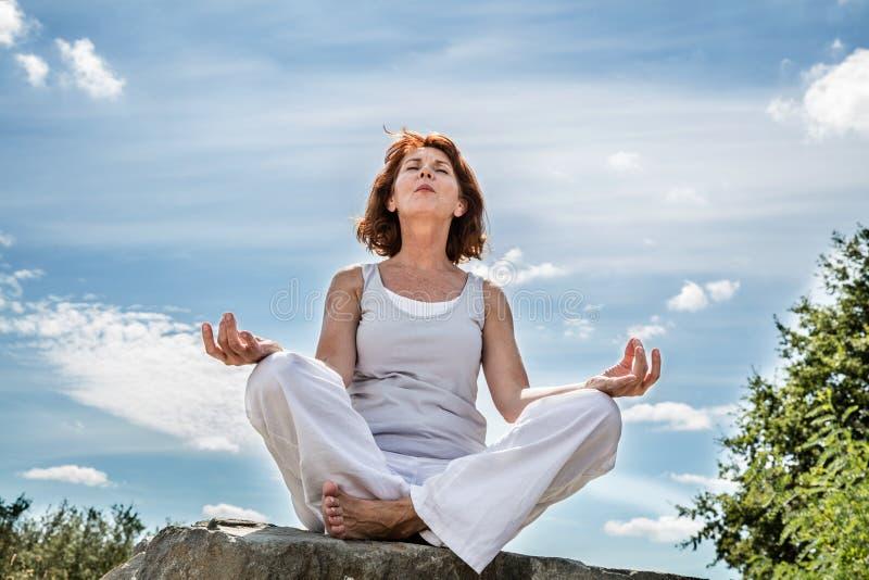 Het uitoefenen in openlucht voor de midden oude zitting van de yogavrouw op een steen stock foto