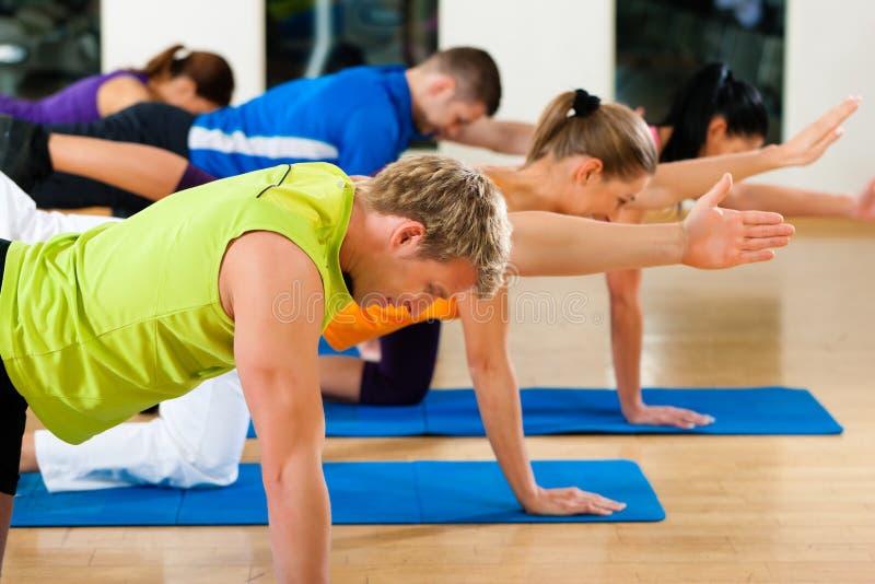 Het uitrekken en gymnastiek zich in geschiktheidsclub of gymnastiek