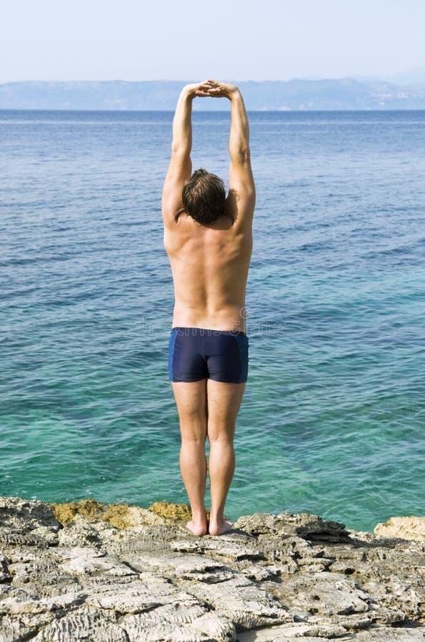 Het uitrekken van de mens zich op strand royalty-vrije stock afbeeldingen