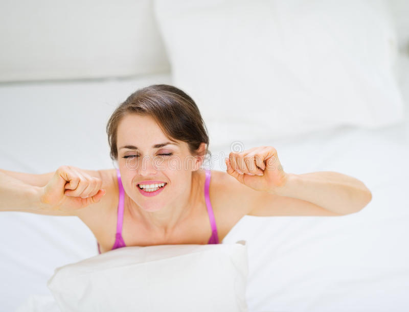 Het uitrekken van de vrouw zich na wakker stock afbeeldingen
