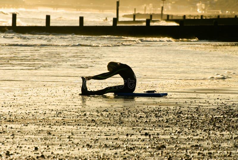 Het uitrekken van Surferr zich op het strand stock afbeelding
