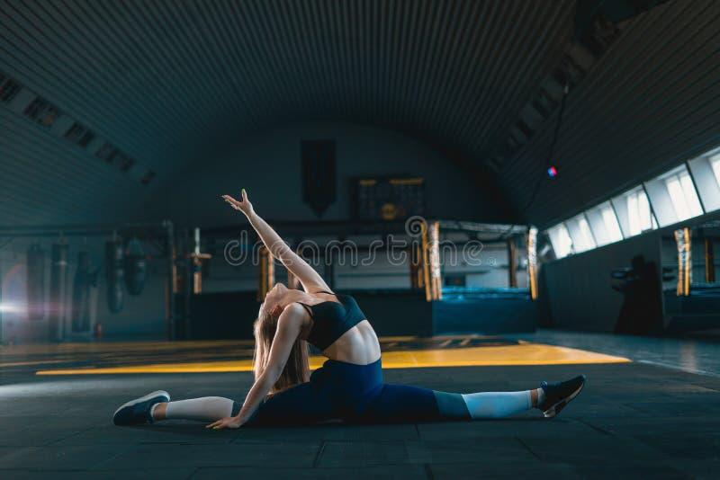 Het uitrekken van turnermeisje die verticale spleet, streng doen Zijaanzicht van aantrekkelijke jonge vrouw die kernoefening doen stock afbeeldingen