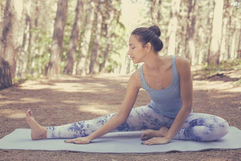 Het uitrekken van vrouw die in openluchtoefening gelukkige het doen yoga glimlachen stock afbeeldingen