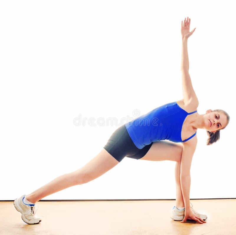 Jonge vrouw die oefeningen doen stock foto