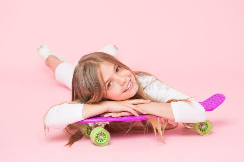 Het uitspreiden van gelukkige trillingen met de stuiverraad Het kleine meisjesschaatser ontspannen bij het dek van de stuiverraad royalty-vrije stock afbeelding
