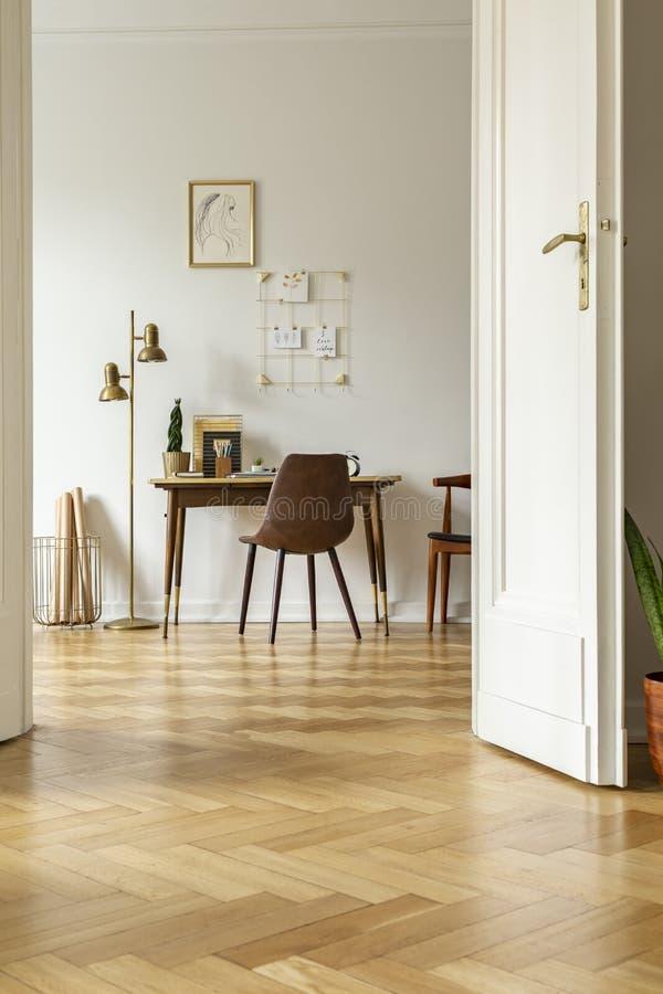 Het uitstekende binnenland van het huisbureau met een bureau, een stoel, een lamp, een grafische en muurorganisator Mening van ee royalty-vrije stock foto