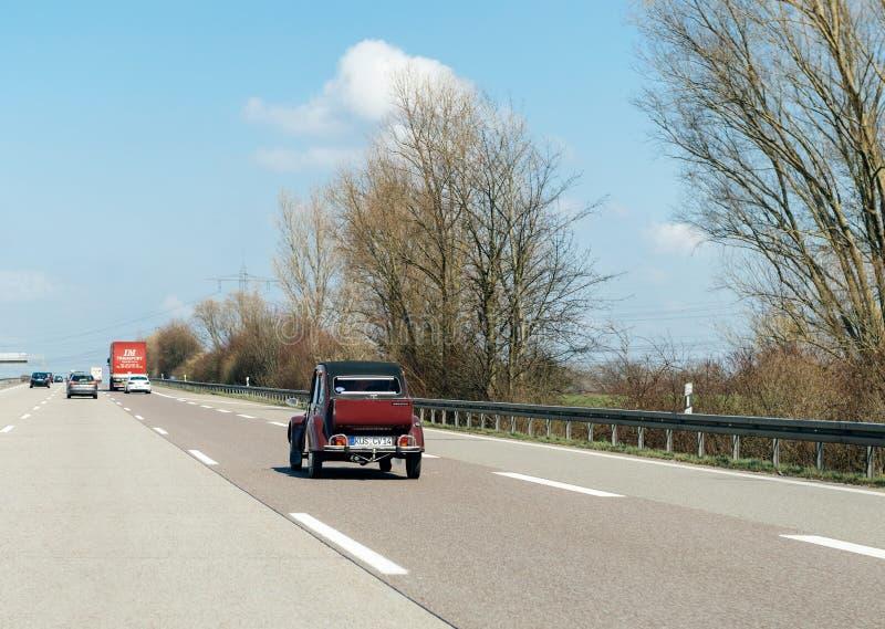 Het uitstekende de auto van Citroën 2CV drijven op weg stock foto