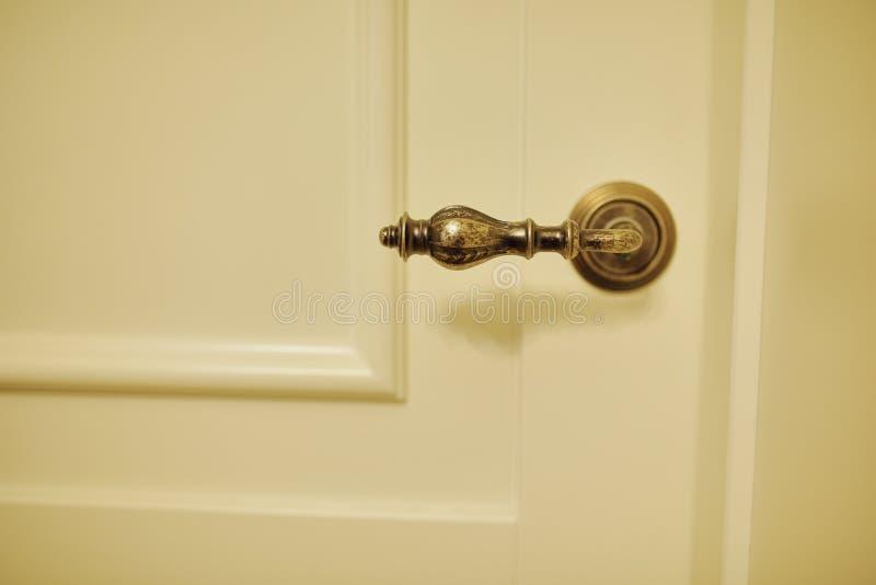 Het uitstekende handvat van het metaalbrons in een houten witte deur royalty-vrije stock fotografie