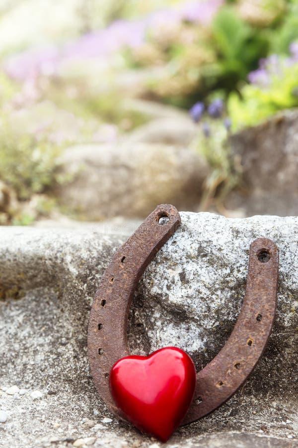 Het uitstekende hoefijzer en rode hart van de groetkaart stock afbeeldingen