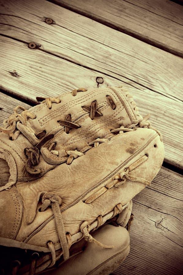 Het uitstekende Kijken Sepia Antieke Honkbalhandschoen op Hout stock fotografie