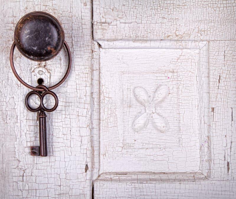 Het uitstekende zeer belangrijke hangen op een uitstekende deur stock afbeeldingen