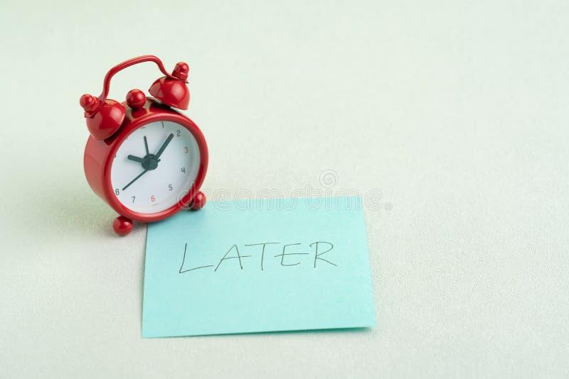 Het uitstel, stelt of het luiheidsconcept, rode wekker op kleverige nota met handschrift het woord later op bureaulijst uit stock afbeelding