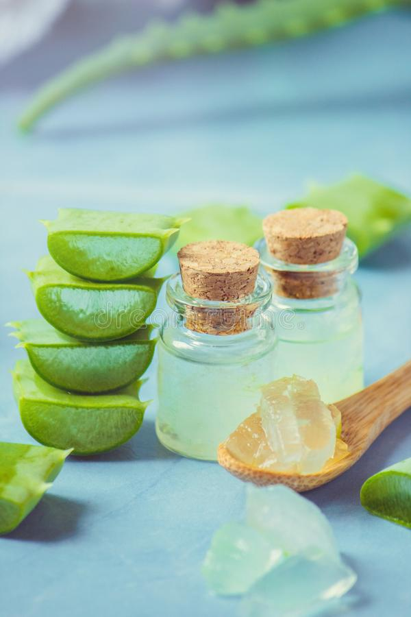 Het uittreksel van aloëvera in een kleine fles en stukken op de lijst stock fotografie