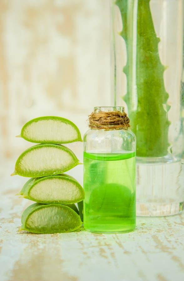 Het uittreksel van aloëvera in een kleine fles en stukken op de lijst stock foto's
