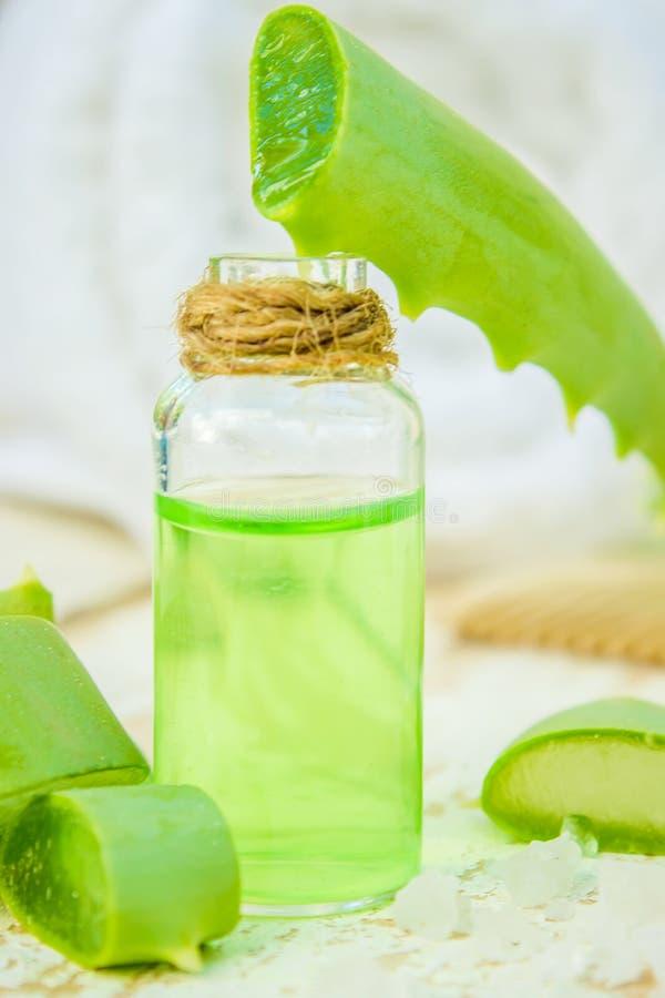 Het uittreksel van aloëvera in een kleine fles en stukken op de lijst royalty-vrije stock afbeeldingen