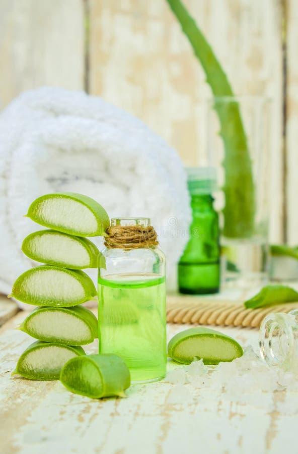 Het uittreksel van aloëvera in een kleine fles en stukken op de lijst royalty-vrije stock afbeelding