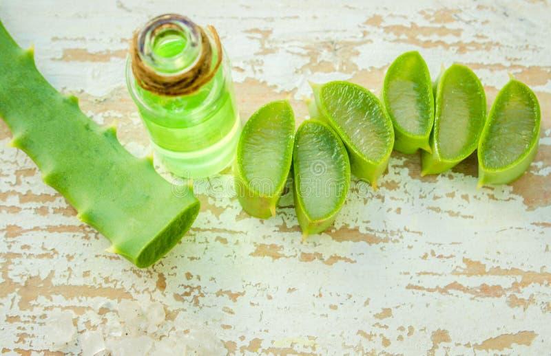 Het uittreksel van aloëvera in een kleine fles en stukken op de lijst stock afbeeldingen