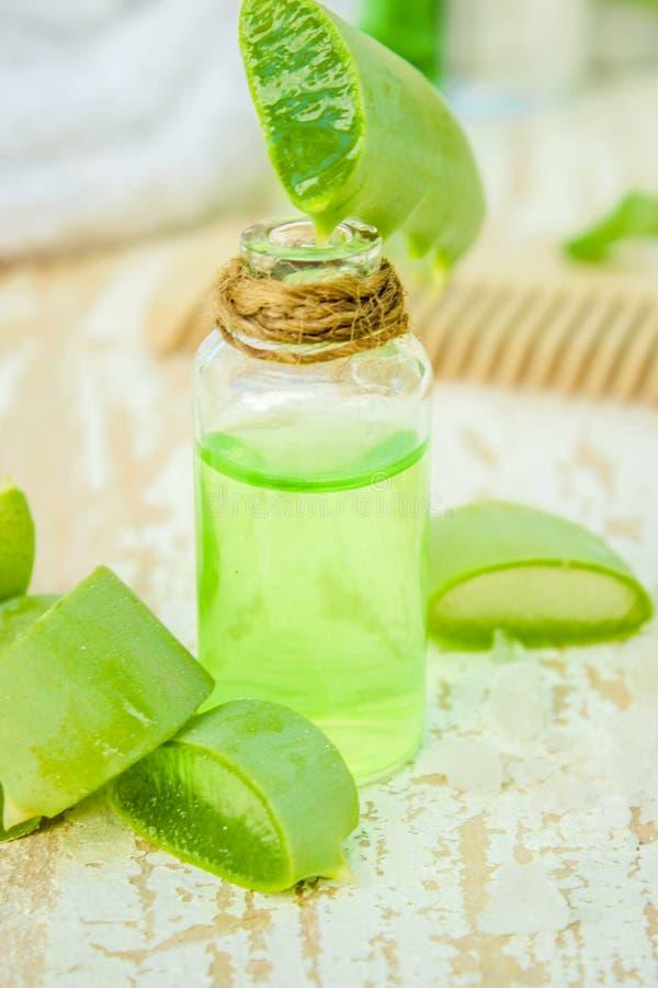 Het uittreksel van aloëvera in een kleine fles en stukken op de lijst royalty-vrije stock foto