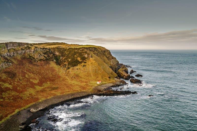 het UK, Noord-Ierland, Provincie Antrim, eenzame fishermans huisvest in de baai van Havenmaan stock afbeeldingen